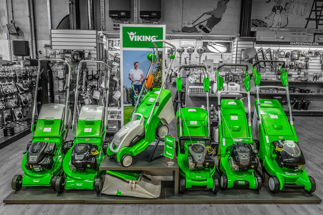 green Viking lawn mowers in a line
